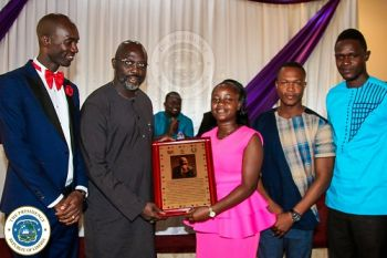 FLY Second Vice President plaque of honor to President Weah as other officials look on