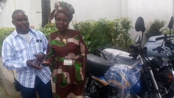 Mr.  Toe K. Wesseh, Coordinator in  the Office of the President presents Motorbike to Marie Zoego of River Cess  County.