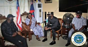 President Weah (left) consoles the bereaved family