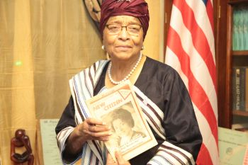 President Sirleaf displays one of  the books in the Library.