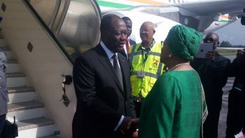 President Sirleaf greets President  Ouattara upon arrival at the RIA.