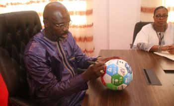 President Weah autographs soccer ball as Deputy Foreign Minister for Legal Affairs Dewey Gray looks on