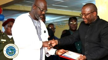President Weah receiving a plague of honor from Hon Emmanuel B Nyeswa, head of the Internal Audit Agency