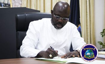 President Weah signing the deed