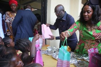 President George Weah and First Lady serving food to children during the program