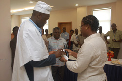 Mrs. Elva M. Richardson, Special Assistant to President presents a gift on behalf of the Ministry of State to Mr. Amara Konneh.