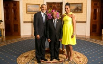 Vice President Joseph Boakai (center) poses with U.S. President Barack Obama (left) and Mrs. Michelle Obama (right).