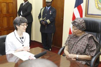 President Sirleaf converses with Her Excellency Mrs. Joanna Marie Adamson, during a ceremony at the President�s Foreign Ministry Office.