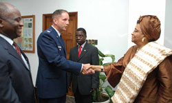 US Military Advisor Colonel James L. Dew Jr. shakes hands with President Ellen Johnson-Sirleaf