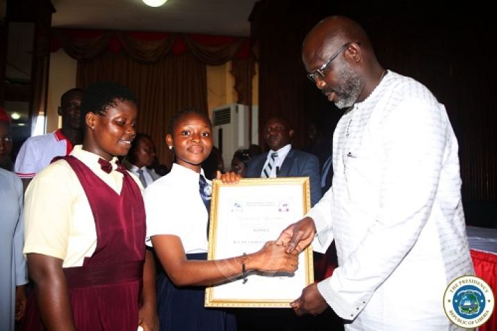 Students presenting a certificate of honor in appreciation of the President's policy to underwrite their WASSCE fees