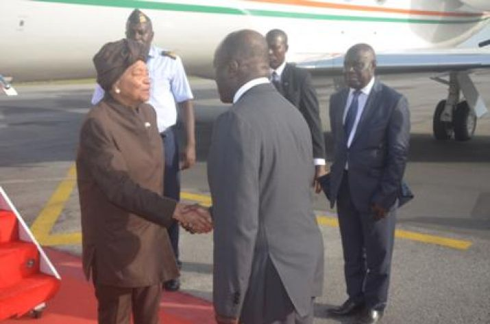President Sirleaf shakes hands with  Vice President of the Republic of Cote d'lvoire upon arrival at the   International Airport in Abidjan.
