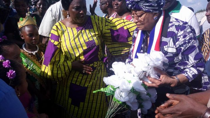 President Sirleaf receives flower  from kid upon arrival in Fuamah District.jpg