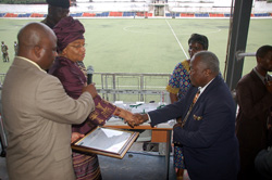 President Sirleaf presents a certificate to one of the honorees at the Antoinette Tubman Stadium in Monrovia.