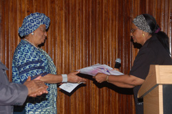 Mrs. Theresa Leigh-Sherman presents the certificate of honor to President Sirleaf.