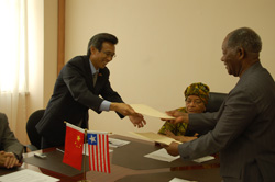 Chinese Ambassador Lin Songtian and Liberia's Foreign Minister George Wallace exchange certificates at the program.
